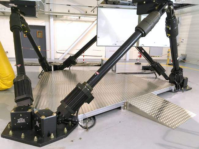 Aluminum platform for access by platform lifts below the flight simulator for maintenance operations